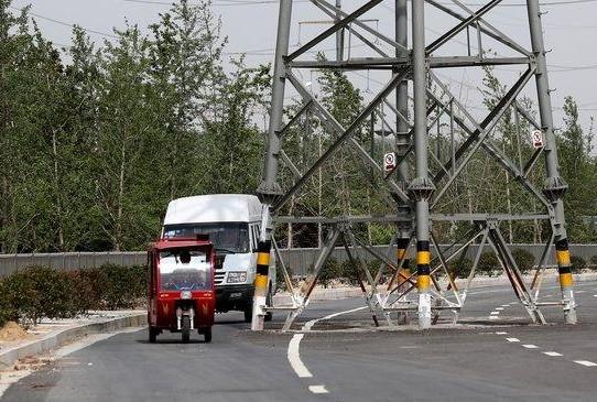 郑州一高压电线塔堵路中央